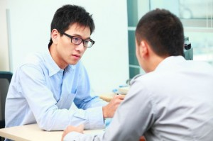 asian businessman talking concerned to other man
